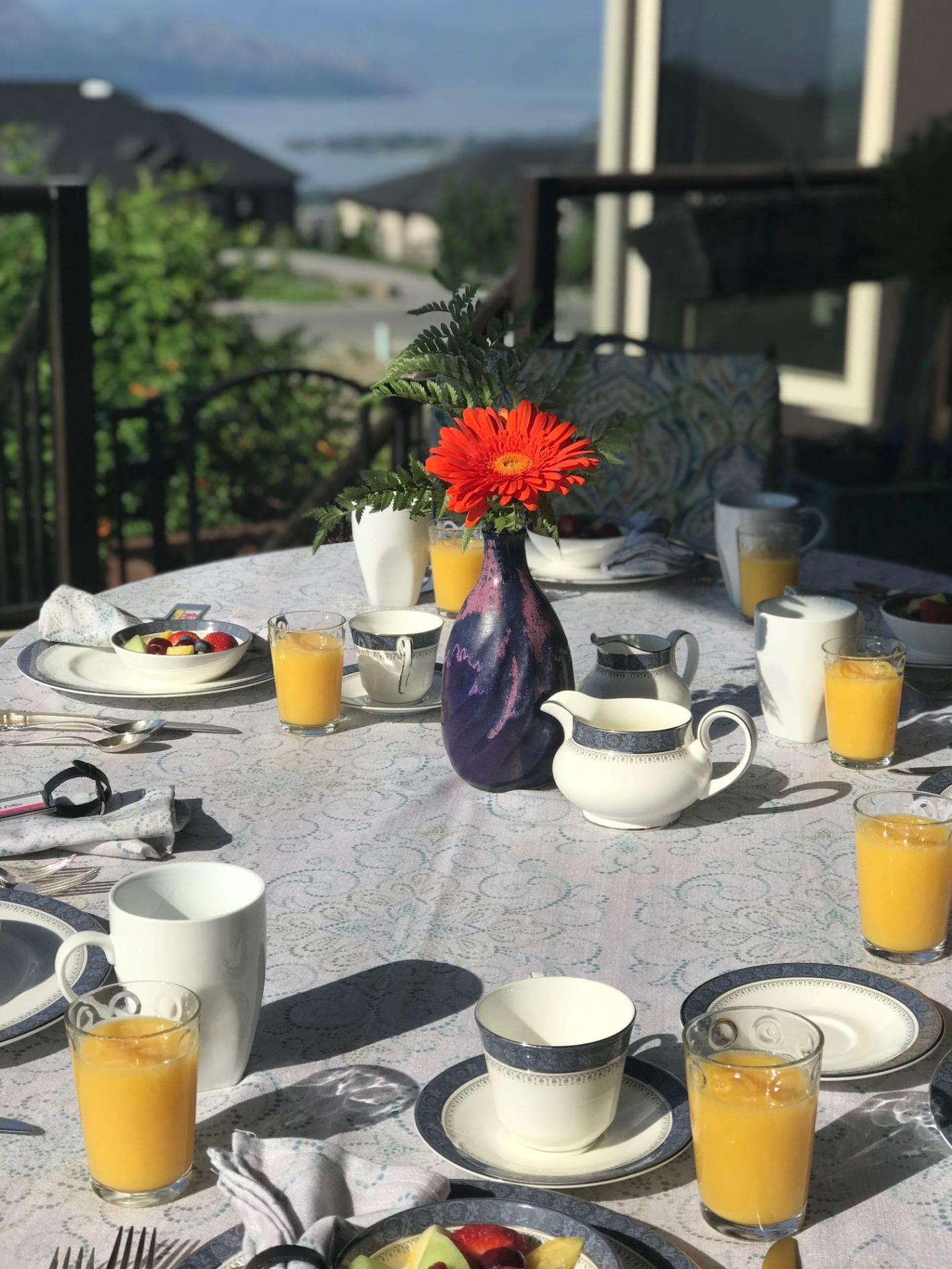 Breakfast Table at Cheers B&B with fruit salad, orange juice, and a floral arrangement