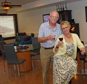 Contact us, Najia and Colin, the Cheers B&B hosts; here sitting with glasses of red wine in their home