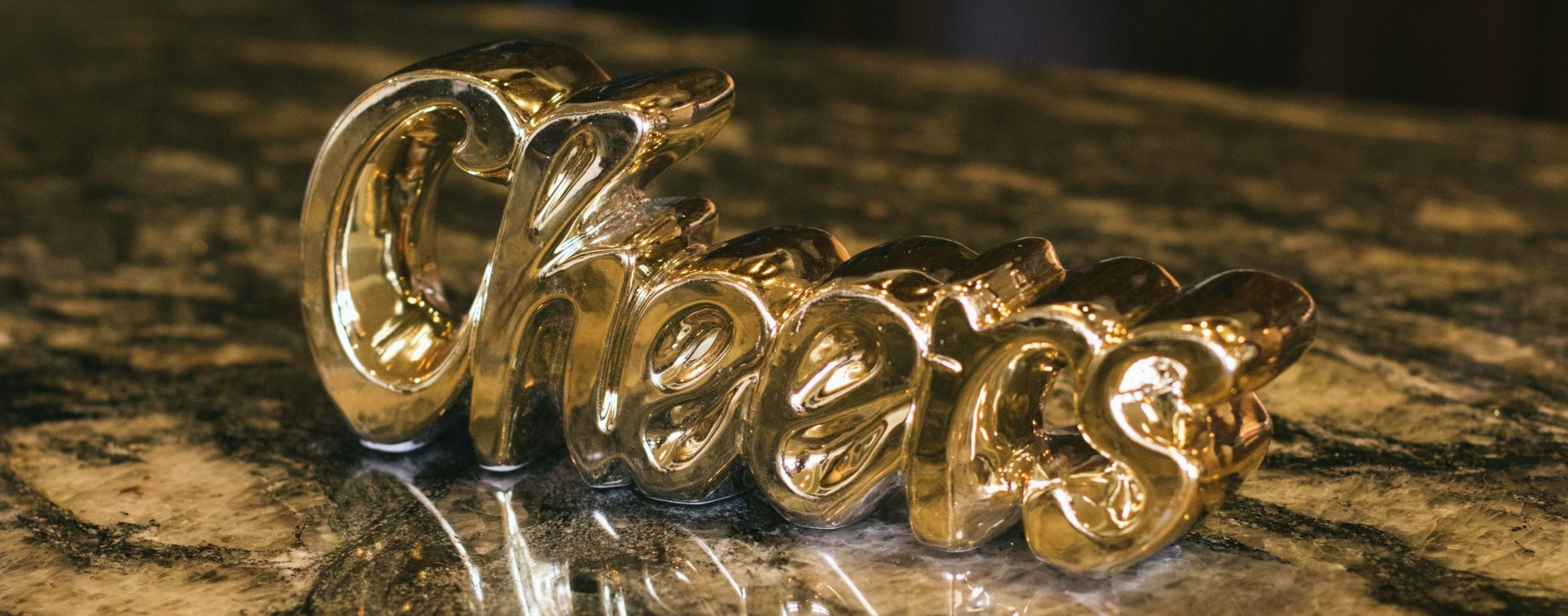 The word 'cheers' in a gold balloon on a wooden surface; highlighting the Cheers Bed and Breakfast, and reinvention