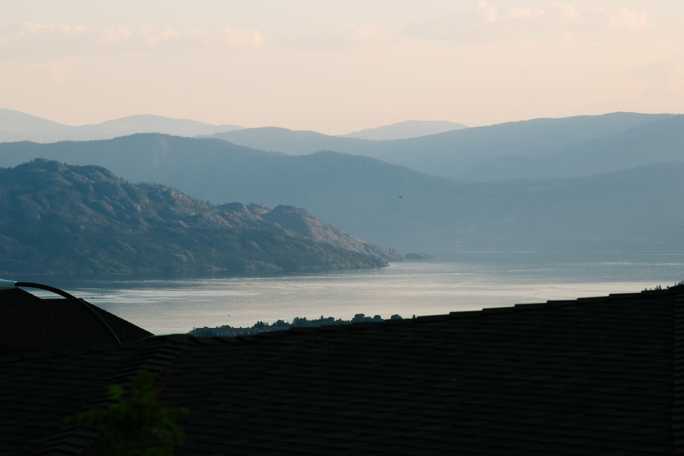 view of a rooftop with the Okanagan lake and hills in the background