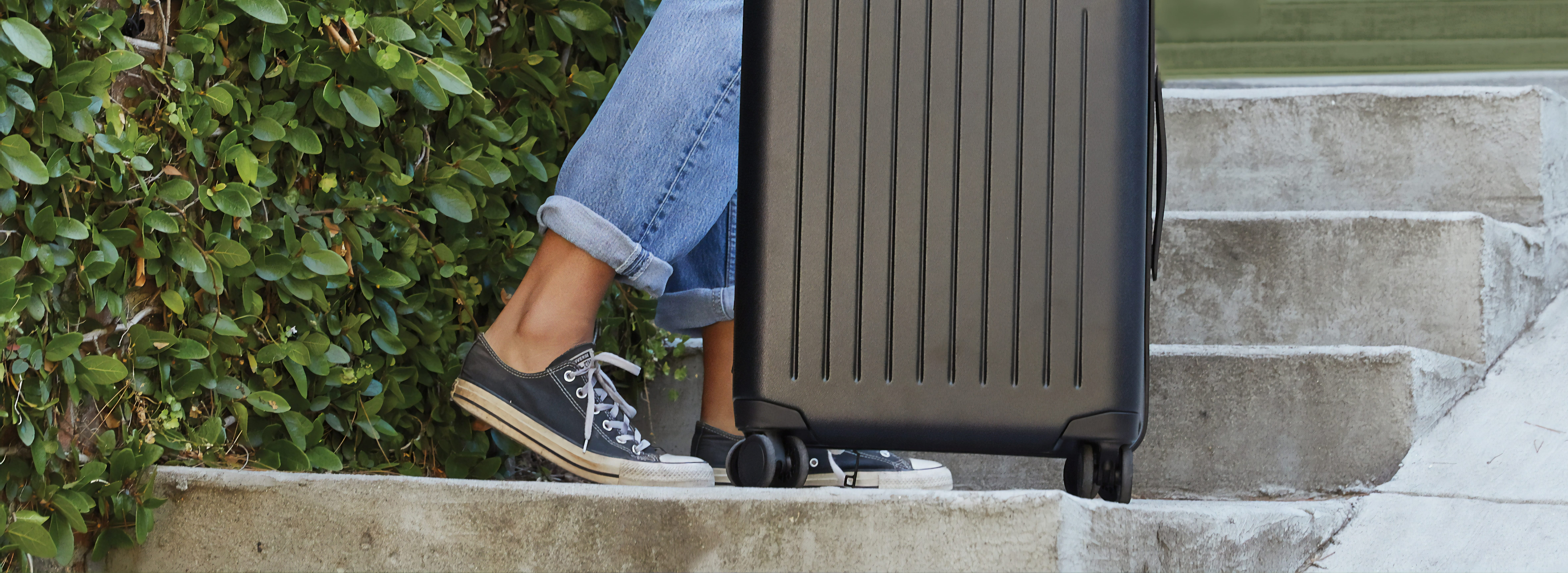 a closeup of a womans shoes and a roller luggage bag on steps, highlighting the benefits of vacation travel